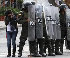 A woman takes cover behind riot police as protesters throw stones during a demonstration in Bogota. FREDY BUILES/REUTERS