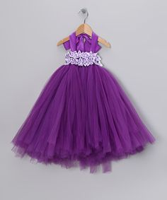 Cute purple dress!! Perfect for tiny twirlers, this frock flaunts two layers of tulle and matching lining, so it's always soft, never itchy. A blossom-covered bodice keeps it securely in place, while a shiny ribbon halter top takes the spotlight. 100% polyesterHand washImported