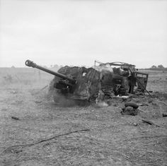 A 17-pdr anti-tank gun and 'Quad' artillery tractor burning on Hill 112 after being hit by mortar fire, 15 July 1944.