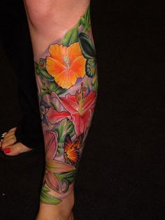 Wow, look at the colors and detail of this calf tattoo containing flowers, a butterfly and more...