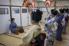 A Okasan (Japanese for mother) teaches protégés a traditional dance using fans