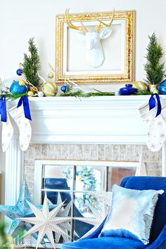 Modern Eclectic Blue and White Christmas Mantel. Love the faux deer head with gilded antlers!