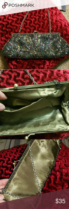 """Vintage clutch Vintage clutch. Glass hand sewn beads. Iridescent Colors: purple, blue, green. Kiss lock closure. Gold satin, lined. One main pocket with one small pocket. Gold chain can fold inside. Chain length 30"""". Great condition! unknown Bags Clutches & Wristlets"""