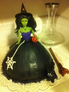 Witch cake. Made like the Barbie princess cakes by baking the cake in a bowl, turned upside down to make the skirt. I painted the doll green with acrylic paint, added yellow and red eyes and a spider necklace with nail polish. Cat is fondant. Hat is card stock. Easy and super cute!