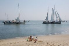 Foto van strand met spelende kinderen, in de verte zeiljachten. (Wadden Sea | Netherlands)