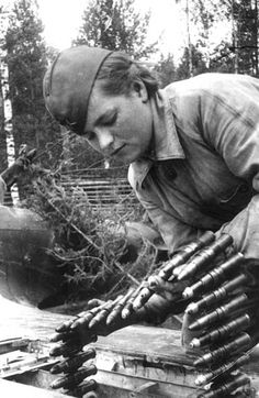 A Soviet shooter is loading a gun with ammunition.