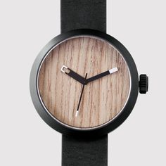 The unisex timepiece has an assuring weight of 110g, featuring a unique natural oak dial with minimal detailing. Key attributes include a matt black PVD co
