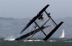 A sailor (L) falls onto the wing of an Oracle Racing AC45 boat after it capsized during an exhibition race to promote the 34th Annual America's Cup, in San Francisco Bay June 13, 2011.  REUTERS/Beck Diefenbach
