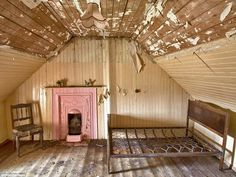 This attic bedroom in a cottage on Lewis has a beautiful original fireplace painted pink -...