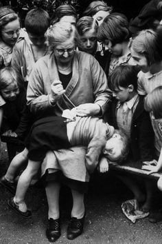 Martha Scott playground attendant at Regent's Park London mending a young boy's trousers, August 1939