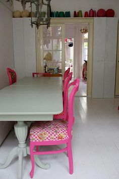 *love* the pink dining chairs and the colored pottery around the ledge in the room.