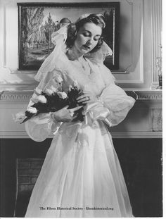 """a.A woman modeling a bridal dress. Description on the back of the reads: """"June 27, 1943.  Bundles for Brides.  Organdy Bride...For Spring and Summer, the bride favors cool, crisp organdy. This one, with its effective eyelet trim, is news because of the matching eyelet cap with organdy shoulder veil. Sleeves are long, tight at the wrist and slightly puffed."""" Al Blunk Collection, The Filson Historical Society."""
