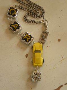 made from a yellow metal toy car and vintage scrabble letters.
