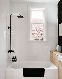 Black and white bathrooms | Black shower and wall contrast with wooden cabinet and white tiles. Design by Fran Woodall, photo by Terence Chin via Sharedesign.