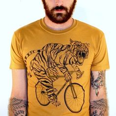 there are just way too many amazing things in this photo:beard.tiger on a bike.tattoos.yellow.