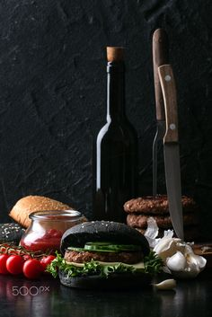 Home made burger with black bun - Home made burger with black buns and meat cutlet, decorated with a branch of cherry tomatoes garlic, and a bottle of olive oil as well as steak fork and knife. Dark Rustic Style