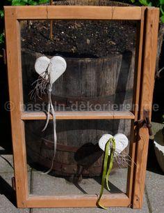 Herzen aus Beton mit einem Satinband und einem kleinen Ästchen dekoriert. Fensterdeko aus Beton.