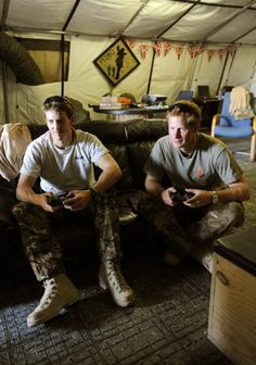 Prince Harry (R) relaxes during computer football game with his fellow Apache helicopter pilot Capt Simon Beattie, during their 12 hour VHR (very high ready-ness) shift on 3 Nov 2012 in Afghanistan