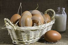A Still Life with a basket of eggs placed on straw, with a bottle of milk in the background on a hessian base
