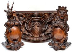 """THE LION & THE ANTELOPE: A pair of beautifully carved beechwood capitols of an Heraldic Lion and an Antelope each seated and holding scrolled cabuchons, together with a carved beech wood plaque depicting the Coat of Arms of the City of Manchester which was granted to the City in 1842 and was derived from the arms of Henry IV. The City's motto is inscribed on the plaque and reads """"Concilio et Labore"""" which losely translated means """"Wisdom and Effort""""."""