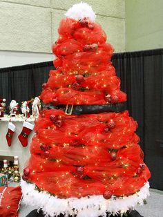 Santa-Inspired Christmas Tree:   Santa comes but once each year -- lengthen his visit by creating a Santa-inspired Christmas tree. Cover a Christmas tree with white lights. Wrap the top and bottom with a white feather boa and the area between with red gossamer and sheer ribbon. Secure a large black belt around the middle of the tree to create Santa's waist. Make gatherings throughout the middle section with red ornament ball clusters, and embellish the tree skirt with a pair of Santa-esque s...