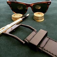 A photoshoot featuring Rayban Wayfarer , Krugerrand billion coins , a 18k gold plated Parker Pen and the KASPARI 5.45 belt