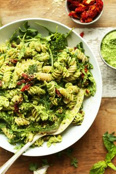 Amazing, 30-minute pea pesto pasta that's vegan, gluten free, and tossed with arugula and sun-dried tomatoes.