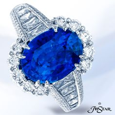 Beautiful JB Star 4.98ct Sri Lankan oval sapphire ring encircled with round diamonds completed with trapezoid diamonds. Platinum.