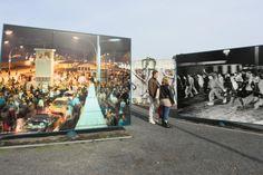 Historische Fotos auf großen Tafeln am frühere Grenzübergang an der Bornholmer Straße in Berlin, heute Platz des 9. November, schauen sich zwei Besucher an. Am 09. November feiert Berlin den 25. Jahretag der Maueröffnung.