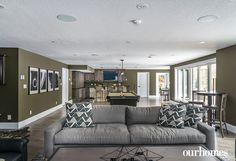 """Whether lounging on the 10-foot sofa, enjoying a game of pool, or sliding up to the bar for a beverage, the lower level was designed to be the ultimate gathering space. The backyard and forest beyond is on full display through the large expanse of windows.    See more of this home in """"Builder Raises his Own House with In-Demand Concepts"""" from OUR HOMES Grey Bruce Spring 2017    http://www.ourhomes.ca/articles/build/article/builder-raises-his-own-house-with-indemand-concepts"""