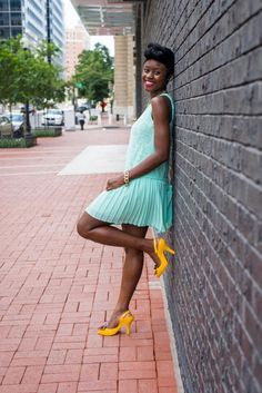 Nife is wearing a bright turquoise dress and yellow Melissa heels. Via Skinny Hipster