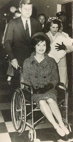 President Kennedy pushing his  wife Jacqueline in a wheelchair after the birth of their son John Jr.
