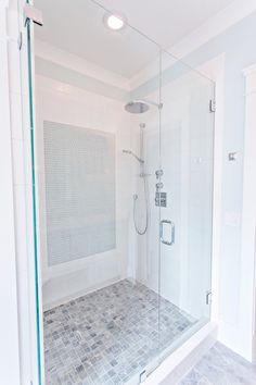 Stunning bathroom features a large walk-in shower with frameless glass front, highlighting an oversize white subway tile surround accented with a panel of blue glass mosaic tile, alongside an adjustable shower head and rainfall shower head over a small square gray marble tiled floor.