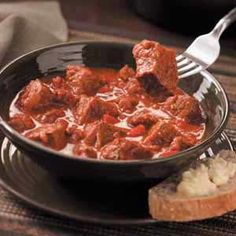 Venison chili con caren-•1 pound bulk hot Ground Sausage  •1 large onion, diced•2 pounds venison steak, cut into 1-1/2-inch cubes  •2 tbls olive oil  •1 can (28 ounces) crushed tomatoes  •1 can (14-1/2 ounces) beef broth  •1/4 cup tomato paste  •1 tsp brown sugar  •2 tsp ground cumin  •2 tsp chili powder  •1 tsp dried oregano  •1/2 tsp crushed red pepper flakes  •Salt & pepper to taste  •1/4 cup minced fresh parsley