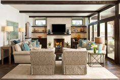 Built-in shelving units on either side of a masonry wood-burning fireplace. Accent pillows pull in the patterned chairs and blue painting. Glass doors lead out onto the patio.
