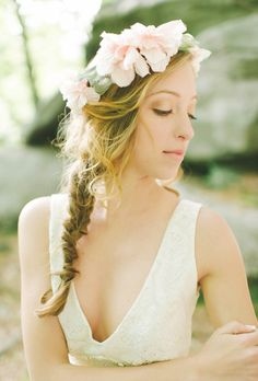 Brides.com: The Prettiest Wedding Hairstyles with Flower Crowns. An Oversize Blush Flower Crown  This bride complements a romantic blush flower crown with a trendy fishtail braid. Balance a bolder style topper with a simple neckline, like this dress's V-neck.