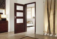 Jasna podłoga, ciemne drzwi, białe listwy przypodłogowe