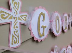 This banner is perfect to hang at such a special occasion as a baptism.  The banner reads God Bless Name. Each scalloped circle and elegant cross measure 5 inches in diameter. The components of this banner are cardstock, tulle and ribbon. The colors shown are pink and gold, one of the most popular color combinations for girls celebrations, also white. If you would like a different color please convo me for availability.  This listing is for names up to 6 letters. Additional letters are $1.50…