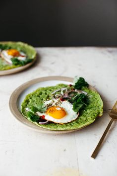 green lachuch with a fried egg, herbs, and cheese