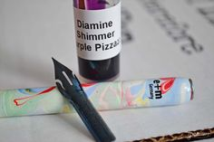 Three of the items that were in the iPenstore November Box - Diamine Shimmer Purple Pizzazz ink sample, Brause Blue Pumpkin Calligraphy Nib, and a calligraphy dip pen holder by E+M Germany.