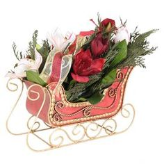 """White and red preservedamaryllis decor with a ribbon accent on a sleigh-inspire base.   Product: SleighConstruction Material: Leaves,  amaryllis, ribbon, and twigsColor: Multi Dimensions: 10.5"""" H x 11"""" W x 10"""" DCleaning and Care: Wipe gently with a dry cloth"""