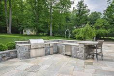 Here's another free standing outdoor kitchen, with large L-shaped stone island holding granite countertops. Full setup includes sink, mini fridge, grill, and barstool seating.