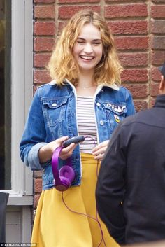 All smiles: Lily looked to be having a jolly time as she held her purple headphones and la...