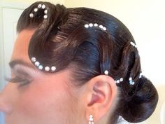 Low bun and large bang swoop. Good hairstyle for standard and latin. Big false lashes and white eye shadow completes the look. Visit http://ballroomguide.com/comp/hair_make_up.html for more hair and makeup info