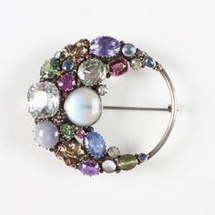 Dorrie Nossiter. A gem-set brooch Unmarked, the open circle applied to one side with a cluster of stones including sapphire, moonstone and peridot, interspersed by leaves, beads and wire tendrils, 5cm diameter. View 3 (Views 1 and 2 from Tadema Gallery).