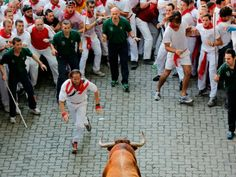 A fighting bull stands alone surrounded by a crowd of runners on the second day of the San Fermin Running..