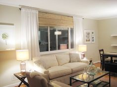 Bamboo shades with curtains.  Curtains hung high above window, blinds used to bridge the gap.  The home owners here actually used two smaller shade side by side and say the texture makes it look seamless, as long as you hang the shades very close.  Awesome and would be cheap with Ikea stuff!  The bamboo shades here are actually from Walmart.