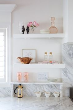 White open shelves with roses and glass vases