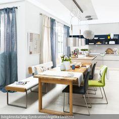 Die moderne Sitzbank mit weißen Lederpolstern peppt die Küche auf, während der Esstisch aus Holz und die Stühle in schwarz und grün farbliche Akzente…