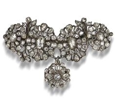 A diamond brooch, late 18th century  Designed as a series of highly stylised floral clusters converted from buttons/dress ornaments, set with cushion, old brilliant and rose-cut diamonds in closed-back settings, mounted in silver, composite, length 7.0cm